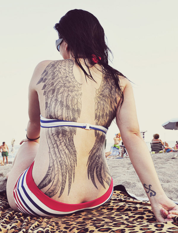 Angel feather tattoo on back