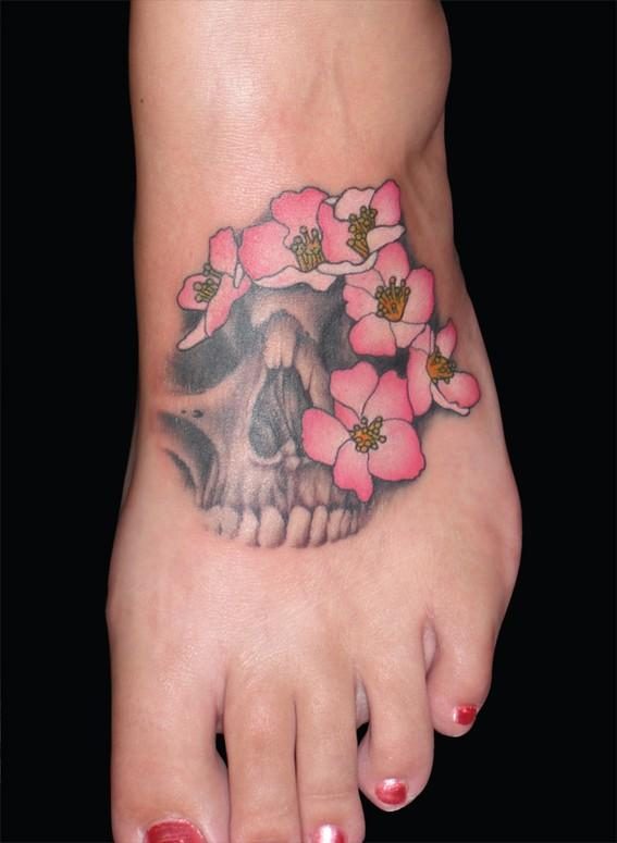 Skull tattoo with flower on foot