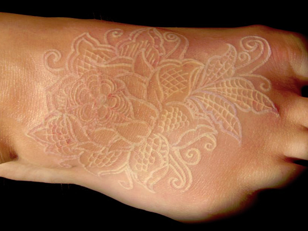 White ink rose tattoo on foot
