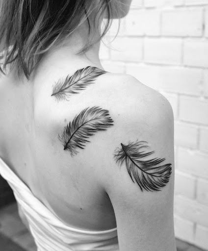Upper back and shoulder feather tattoo