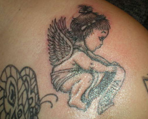 baby angel with wings holding a ribbon Tattoo